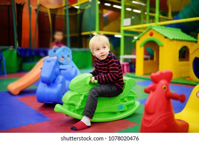 Happy little boy having fun with plastic toy-swing/hopping motorbike in play center. Child playing on indoor playground. Active birthday party for preschooler kids.