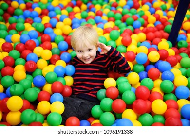 Happy little boy having fun in ball pit with colorful balls. Child playing on indoor playground. Kid jumping in ball pool.