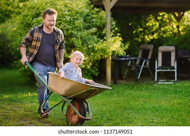 Happy little boy having fun in a wheelbarrow pushing by dad in domestic garden on warm sunny day. Active outdoors games for kids in summer.