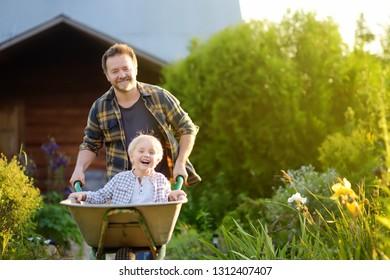 Fröhlicher kleiner Junge, der sich in einer Rollkarre amüsiert und an einem warmen Sonnentag bei Papa im Garten vorbeischaut. Aktive Spiele im Freien für Kinder im Sommer.