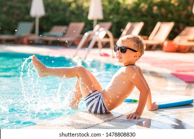 Happy little boy having fun at the pool at the resort