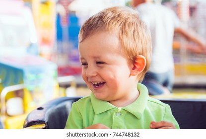 Happy little boy having fun in a carousel
