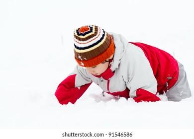 Happy Little boy having fun in the snow