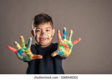 happy little boy with her hands painted on a gray background