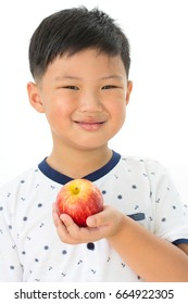 Happy little boy holding a fresh red apple isolated on white background