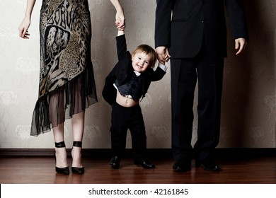 happy little boy holding his parents by the hand
