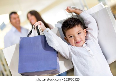 Happy little boy holding shopping bags with his family
