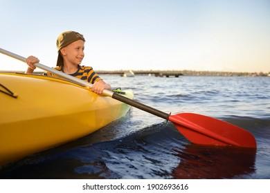 Happy little boy kayaking on river. Summer camp activity