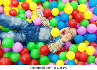 Happy little boy laughing in colorful balls.
