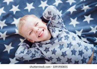happy little boy laughs on stars blanket
