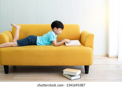 Happy little boy laying down on yellow couch or sofa reading a book over white wall background