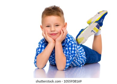 Happy little boy lies on the floor in the studio on a white background. The concept of a happy childhood, rest and vacation. Isolated.