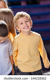 Happy little boy looking away with friends in kindergarten