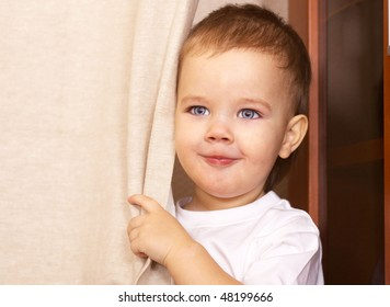 happy little boy looking out from behind curtain