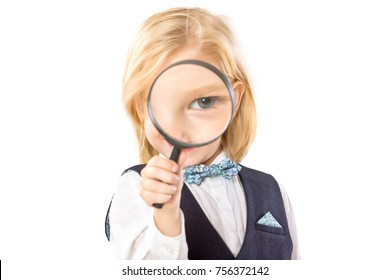 Happy little boy is looking through magnifying glass isolated at white background.