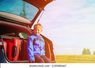 happy little boy with luggage travel by car in nature