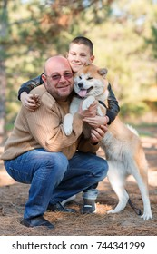 Happy little boy and man walking with dog in the park. Animal concept.