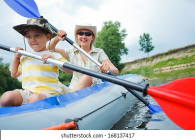 Happy little boy with mother paddling kayak on the river in lovely summer day