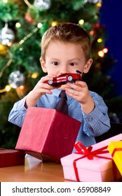 Happy little boy opening Christmas gifts near New Year's tree