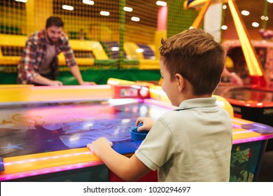 Happy little boy playing air hockey with his dad at Arcade centre