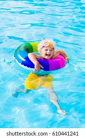 Happy little boy playing with colorful inflatable ring in outdoor swimming pool on hot summer day. Kids learn to swim. Child water toys. Children play in tropical resort. Family beach vacation