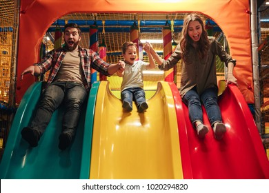Happy little boy playing on a slide with his parents at Arcade centre