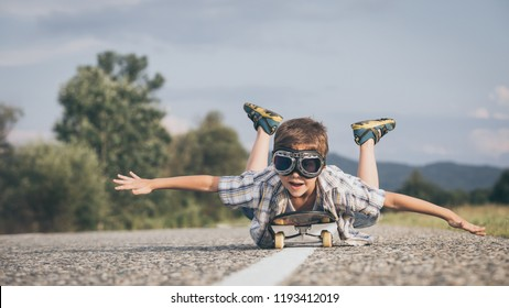Happy little boy playing on the road at the day time. Kid having fun outdoors. He skateboarding on the road. Concept of sport.
