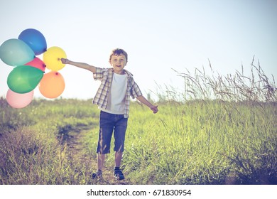 Happy little boy playing on road at the day time. He running in the field and holding in hands  balloons. Kid having fun on the nature. Concept of happiness.
