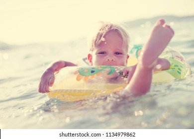 Happy little boy playing in the sea on a tropical resort at the sea. selective focus/ Summer relax concept