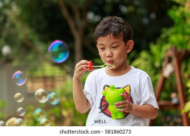 Happy little boy playing with soap bubble in summer, green garden background.