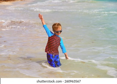 happy little boy playing in waves at summer beach