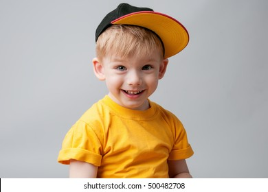 Happy little boy poses on a gray background. He wearing a yellow cap. Hip-Hop Style. Studio shot
