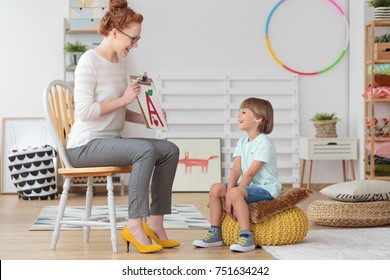 Happy little boy with pronunciation and language difficulties during speech therapy session with young female doctor