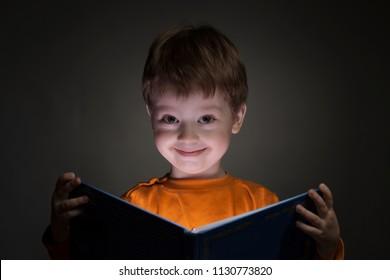 happy little boy read book on black background.