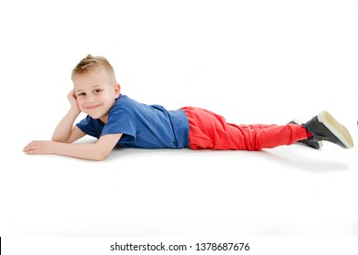 A happy little boy rests on the white background