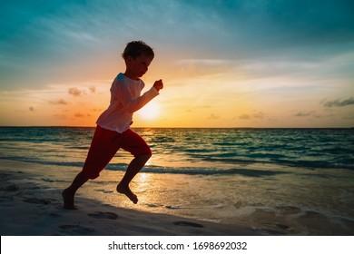 happy little boy run on sunset beach