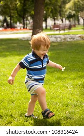 happy little boy running in garden with mouth open