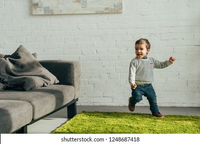 happy little boy running in living room at home