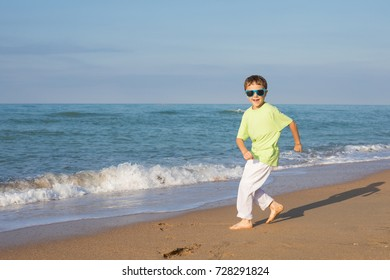 happy little boy running on the beach at the day time. Kid having fun outdoors. Concept of  summer vacation.