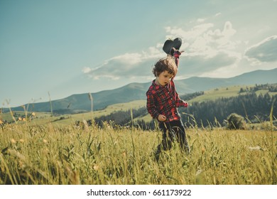 Happy little boy running over the top of the mountain. A child with a hat in his hand on a hill of the mountain. Carpathian mountains