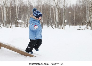 Happy little boy runs on log in park during snowfall at winter day