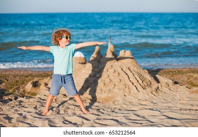 happy little boy and sandcastle on tropical beach, kid playing on a beach, boy build a sand castle at the sea shore, family vacation on a tropical island, child on the background of summer sea