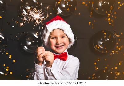 happy little boy in santa claus hat holding sparkler. Christmas Eve
