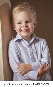 Happy little boy in shirt posing at the wall