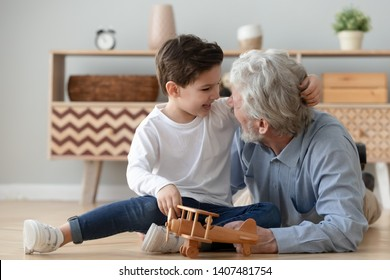 Happy little boy sit on floor laughing hug cuddle having fun with smiling loving grandfather, overjoyed grandparent enjoy relaxing playing with wooden plane entertain with small grandson at home
