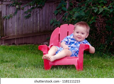 happy little boy sits in the garden in a small red chair
