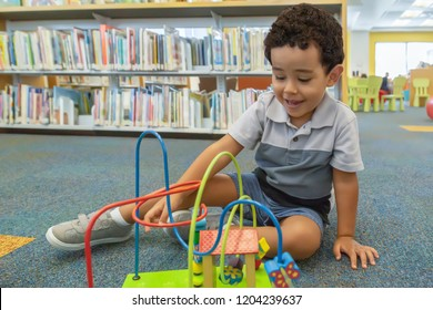 A happy little boy sits on the carpet playing at the library. Off to the side of the class, a a child plays alone.