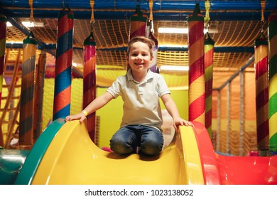 Happy little boy sitting on a slide at Arcade centre