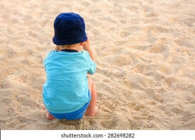 happy little boy sitting on beach at the dawn time