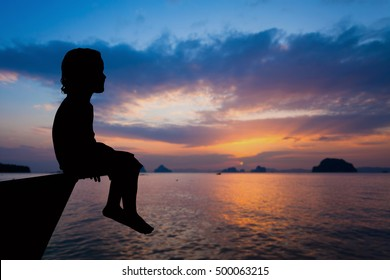 happy little boy sitting on beach at the dawn time. Concept of life.